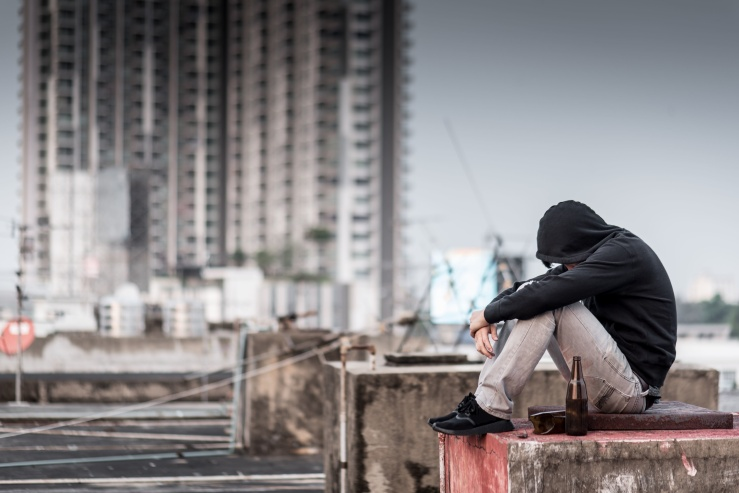 Mystery man in hoody jacket, sitting and hugs his knees up with an empty and broken bottle. depression self destruction suicidal addicts drug, Major depressive disorder concept